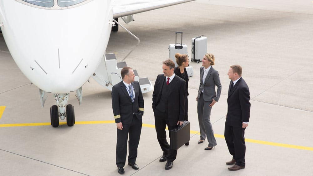 Business people next to a jet