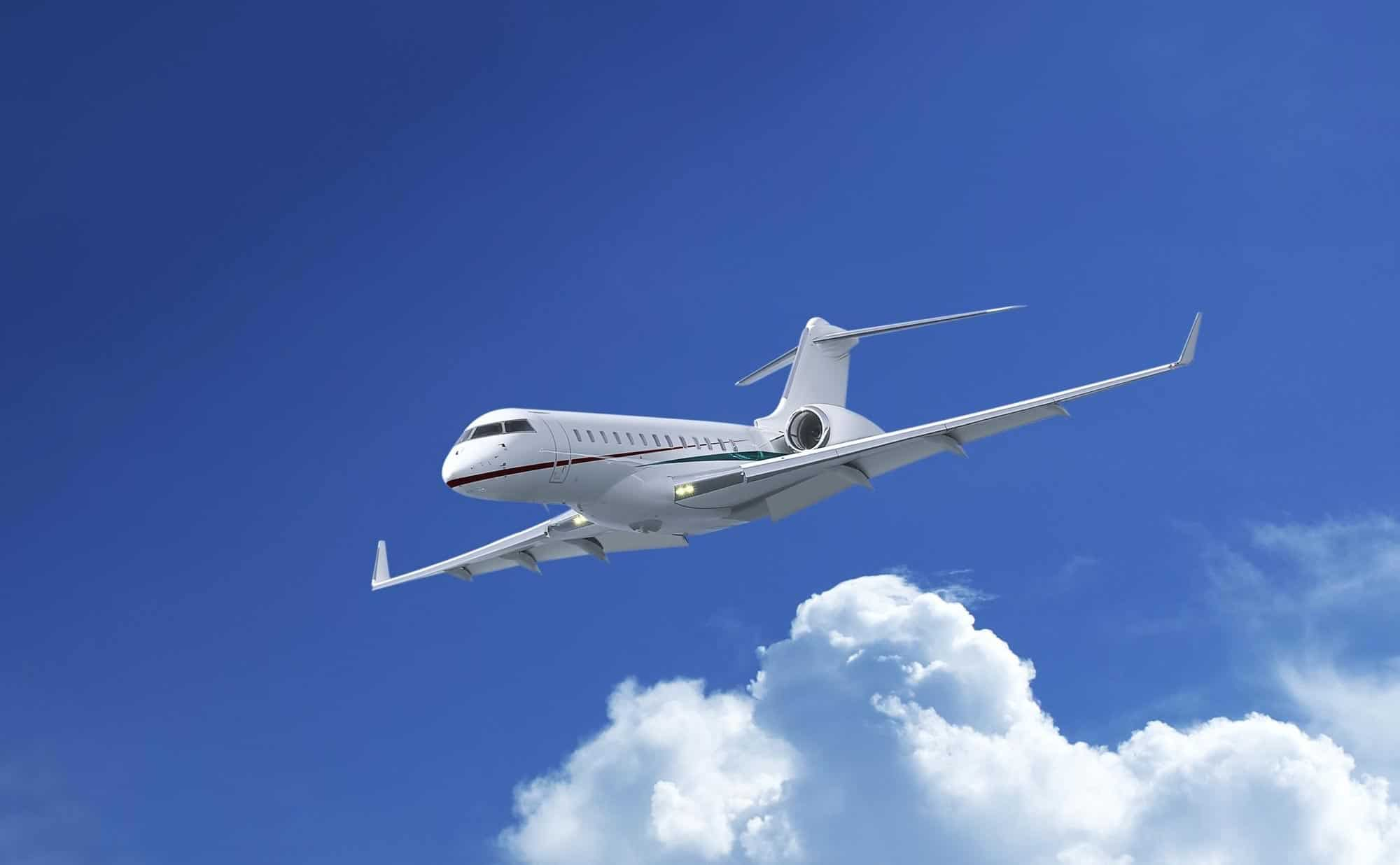 White color private jet in a blue sky with clouds