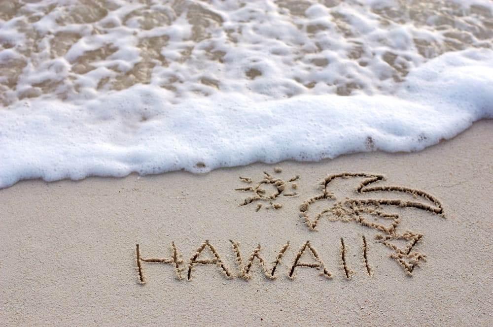 Nice Hawaii note written on white sand with ocean waves on background