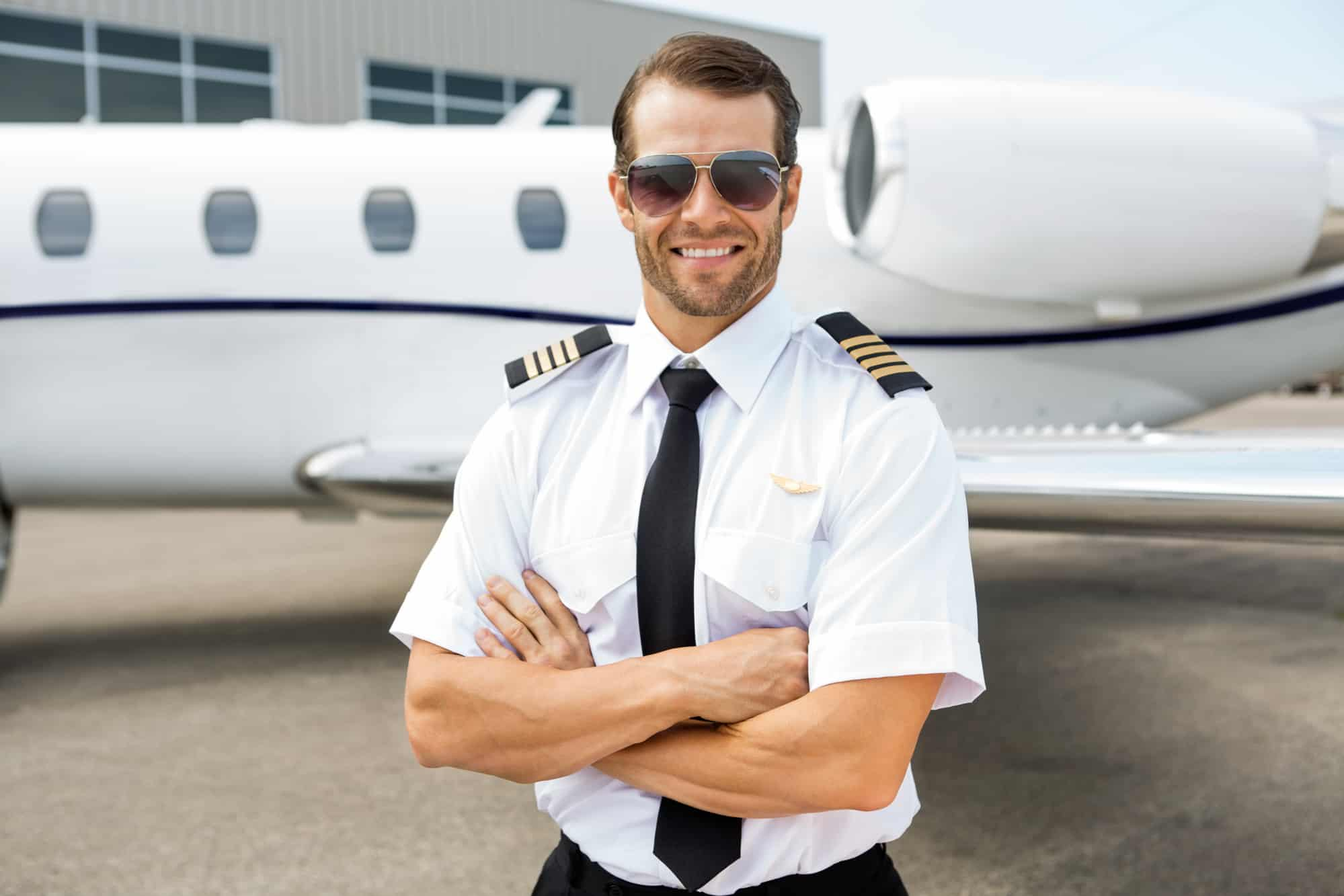 a pilot standing in front of a private jet