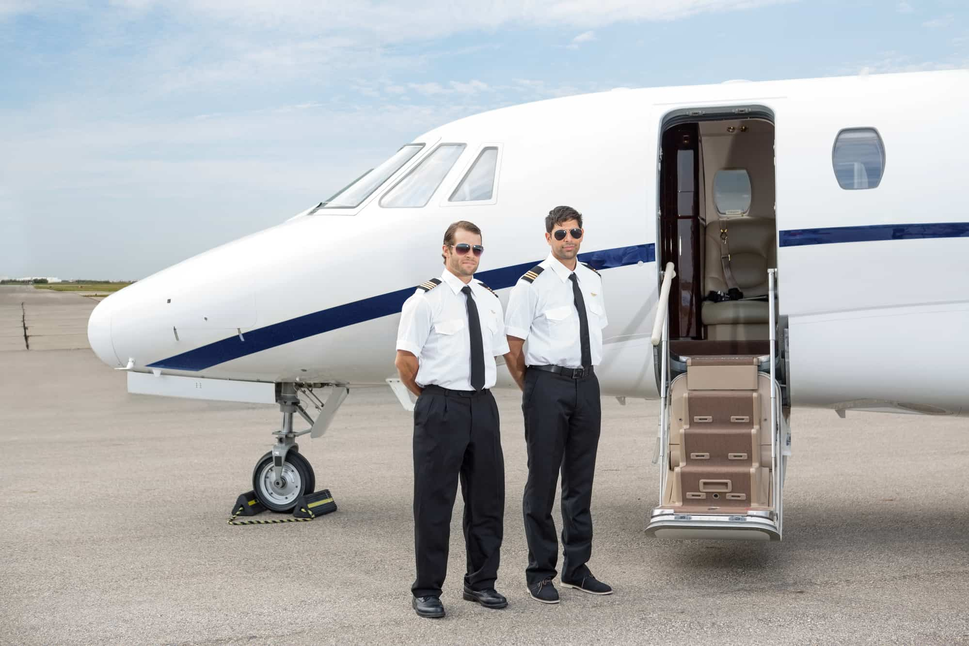 two private jet pilots waiting next to a private jet