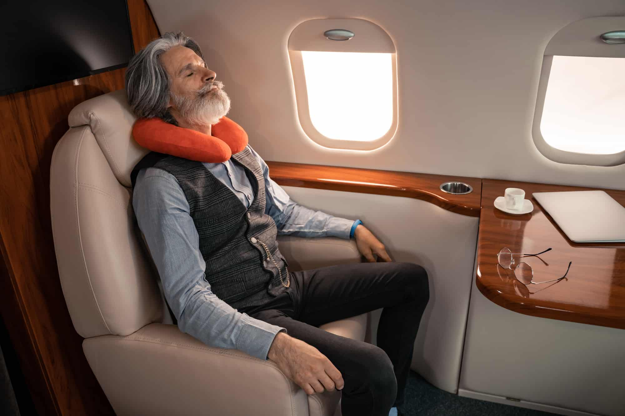 an elderly businessman comfortably resting in a private jet.