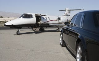 A luxury car parked at a private jet ready to take off.